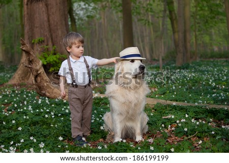 Two years old boy putting a hat on his dog  - stock photo