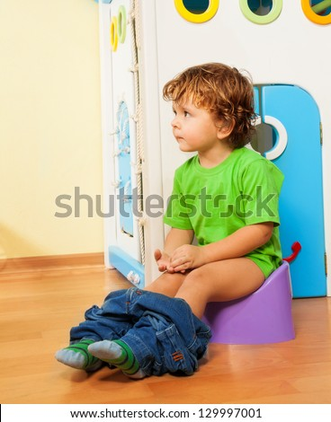 Two years old boy sitting on a potty with his pants off - stock photo