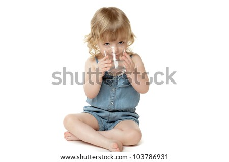 Two years old child sitting on the floor with glass of water, over white - stock photo