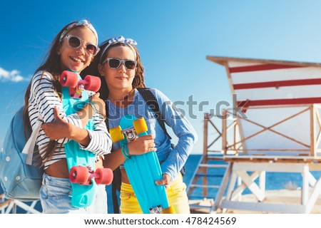 Two 10 years old children wearing cool clothing posing with colorful skateboards on the beach, urban style, pre teen summer fashion.