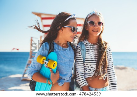 Two 10 years old children wearing cool clothing posing with colorful skateboards on the beach in sunlight, urban style, pre teen summer fashion.
