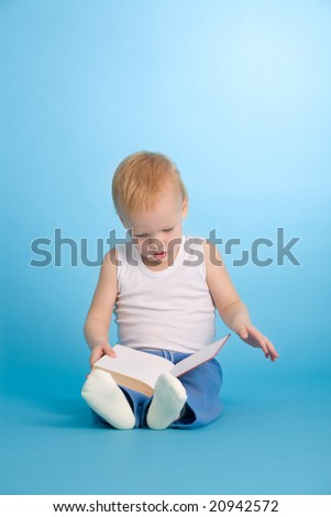 Two years old cute boy reading a book over blue background - stock photo