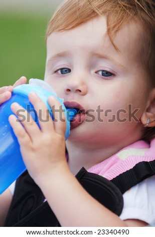 Two years old girl child drinking from blue bobtle