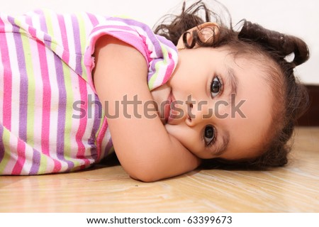 Two years old girl lying on the floor