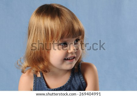 Two years old girl on blue background at studio, closeup portrait. She is smiling. - stock photo
