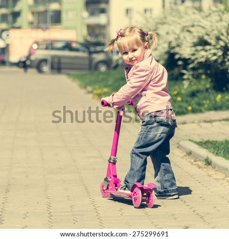 Two years old girl riding her scooter on the street - stock photo