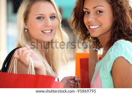 two 20 years old girls, a blonde and a metis doing shopping - stock photo