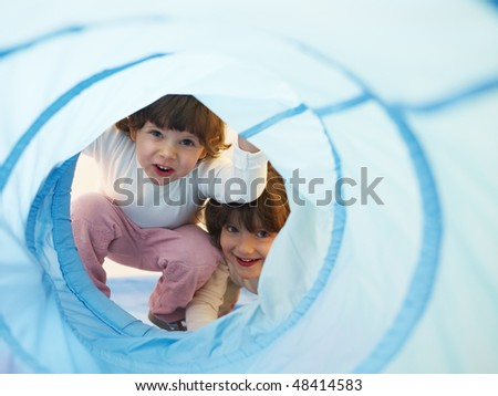 two 2-3 years old girls peeking from blue toy tunnel. Horizontal shape, Copy space - stock photo