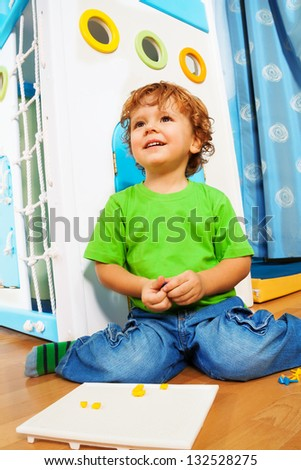 Two years old kid assembling mosaic sitting in his room - stock photo
