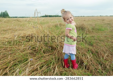 Two years old preschooler girl is looking over her shoulder among farm field floral covering - stock photo