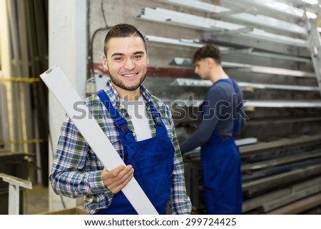 Two 30-35 years-old workers choosing PVC window profile at stand - stock photo