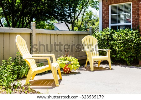 Two yellow adirondack chairs on a patio by fence