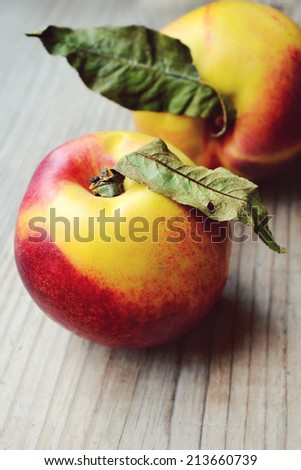 Two yellow and red nectarines with leaves on wooden table