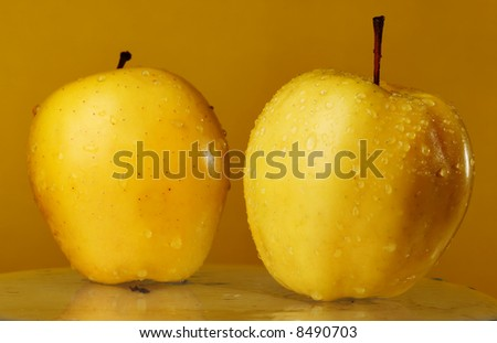 Two yellow apples on the glass over yellow background.