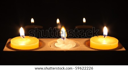 two yellow candles with a white flower in the centre