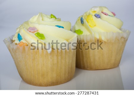Two yellow cupcakes together on a white background - stock photo