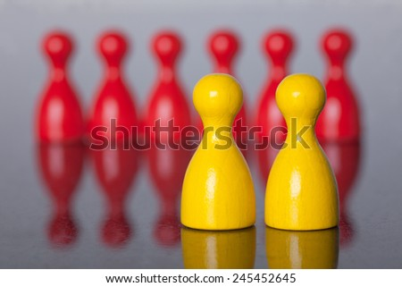 Two yellow figures in front of many red figures . leading character. - stock photo