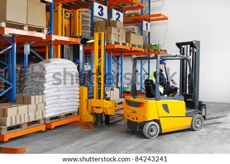 Two yellow forklift vehicles  in distribution warehouse - stock photo
