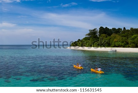 Two yellow kayaks next to a tropical exotic island with blue transparent water - stock photo