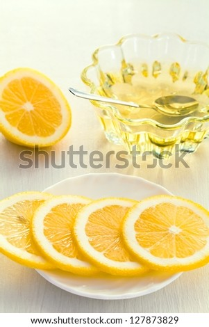 Two yellow lemon and honey glass cup on a white background - stock photo