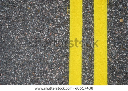 Two yellow lines are painted on asphalt surfacing. The highway is photographed closely. There is copy space. - stock photo