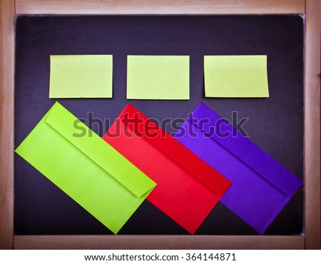 two yellow papers and three colored envelopes on an old black chalkboard
