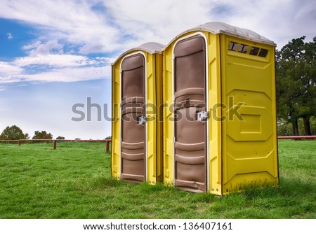 Two yellow portable toilets at a park - stock photo