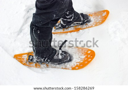 Two yellow snowshoes in the snow - stock photo