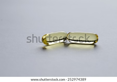 Two yellow transparent capsules on light background. - stock photo