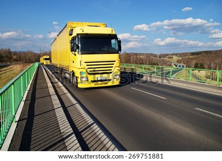 Two yellow trucks driving across the bridge over the motorway. Landscape with highway early spring in the background. White clouds in the blue sky. - stock photo