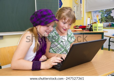 Two you children working on a notebook at school. - stock photo