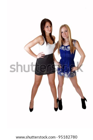Two young a pretty woman, one in a blue dress, the other one in a gray white dress and high heels standing in the studio for white background. - stock photo