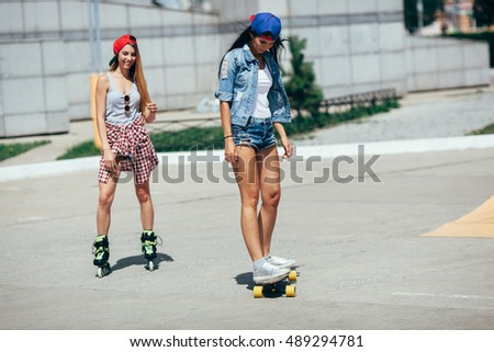 two young adult girls riding on the street
