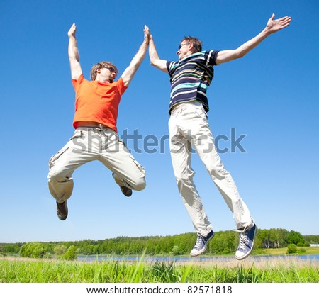 two young adult men jump into the air and clap their hands - stock photo