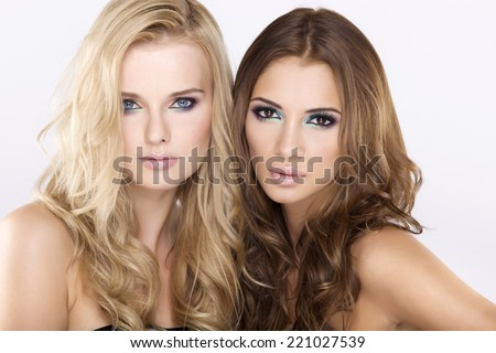 Two young adult sensuality and attractive pretty girl friends - blond and brunette woman on white background - stock photo