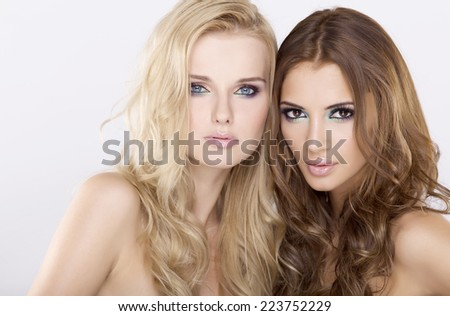 Two young adult smiling attractive sensuality beauty girl friends - blond and brunette pretty woman on white background - stock photo