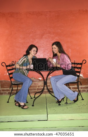 Two young adult women sitting in a cafe, having coffee and using a laptop. Vertical shot.