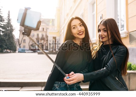 Two young adult women sitting on the bench and make selfie - stock photo