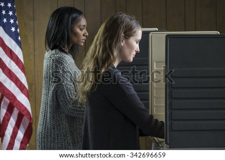 Two young adult women voting in a voting booth - stock photo