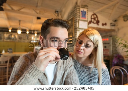 Two young adults (couple) in a cafe. Focus on the closer person, narrow depth of field with only  natural light. - stock photo