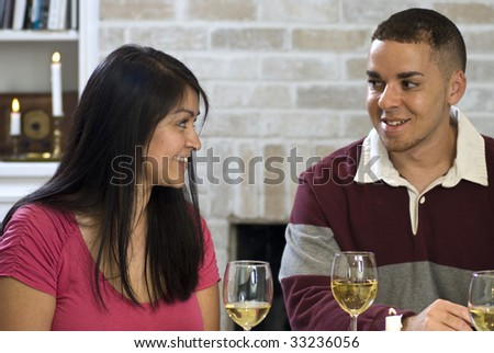 Two young adults enjoying a glass of wine together. - stock photo