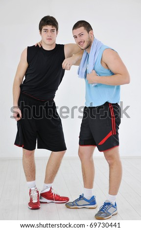 two young adults exercise fitness jumping and relaxing at sport gym club - stock photo