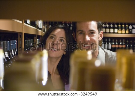 Two young adults looking at wine bottles - stock photo
