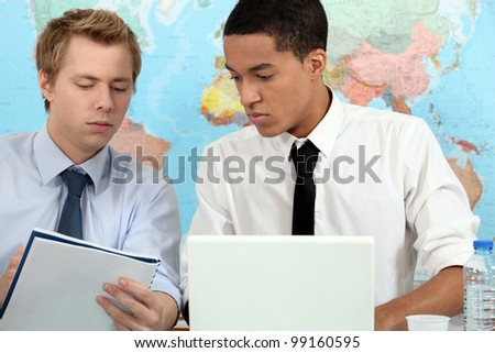 Two young adults preparing student presentation - stock photo