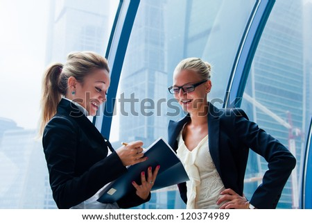 Two young and beautiful business women discussing a business project - stock photo