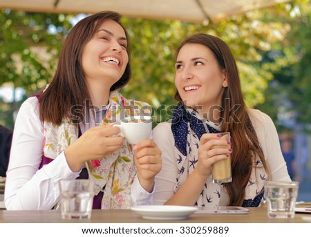Two young and beautiful girls gossiping