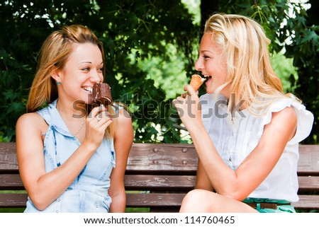 Two young and beautiful woman eating ice cream on a bench in the park - stock photo