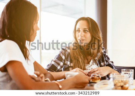 Two young and beautiful women meet at the bar for a cappuccino and to chat. A woman holds in her hands the cup with cappuccino while watching her friend - stock photo