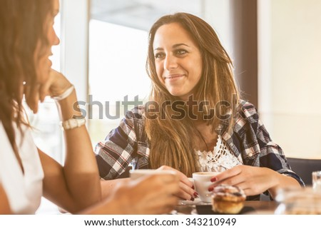 Two young and beautiful women meet at the bar for a cappuccino and to chat. A woman looks smiling and supports the chin with his hand the other looks at her and smiles - stock photo