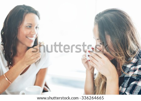 Two young and beautiful women meet at the bar for a cappuccino and to chat. A woman speaks while the other drinks from the cup ceramic - stock photo